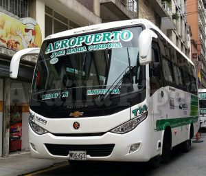 """The buses of Medellin dedicated to the Medellin Airport - city center ride are white and green with """"airport"""" written on the windshield."""