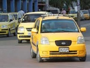 A group of yellow taxis are driving on an avenue of Medellin. Yellow is the color of the official taxis in Medellin.