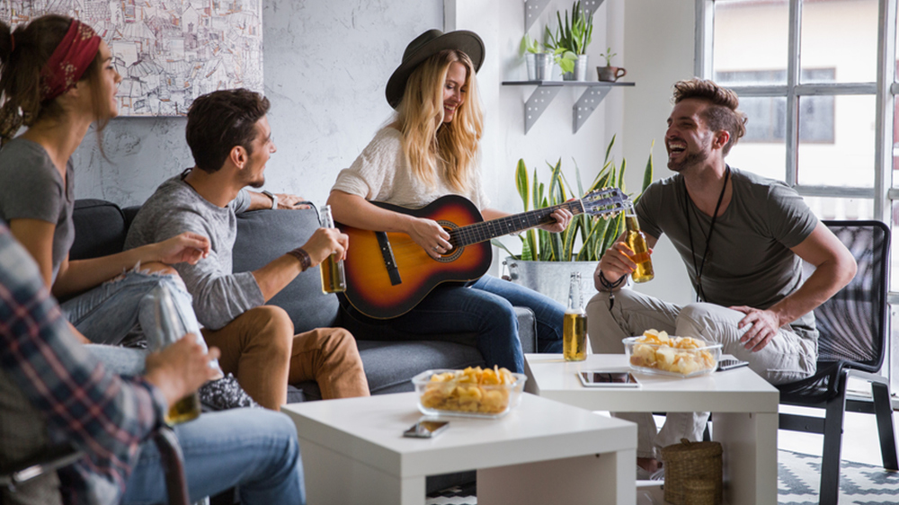 4 roommates are having drinks in their shared housing. They are drinking beers, playing the guitar and laughing in the living room of their modern apartment.