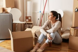 A young woman is sitting on the floor of her house in the middle of cardboard boxes because she is moving out.