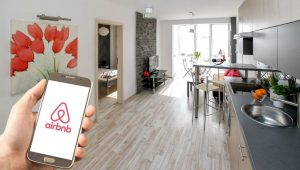 Modern and light apartment with someone holding a phone. The screen of the phone shows the logo of Airbnb